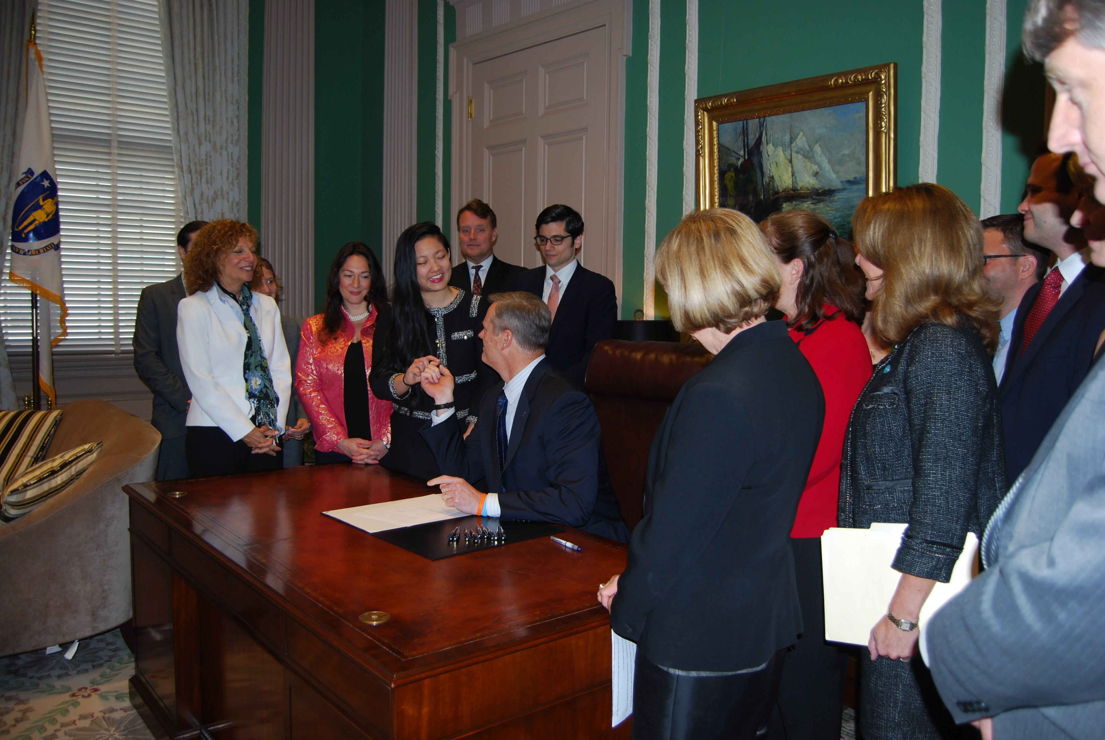 Governor Baker signs H. 4364 and hands a pen to Amanda Nguyen.