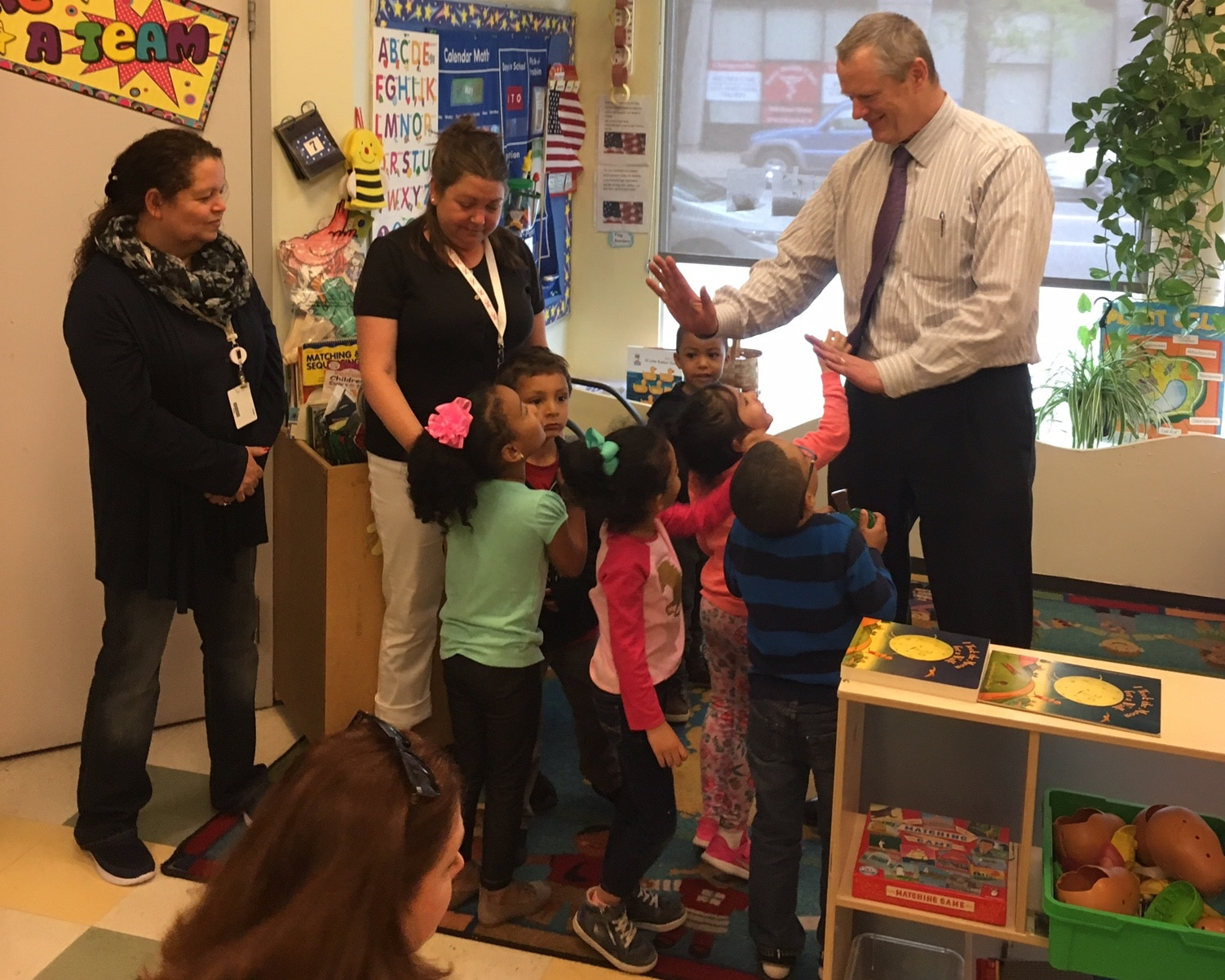 Photo of Governor Baker greeting children in a preschool classroom.