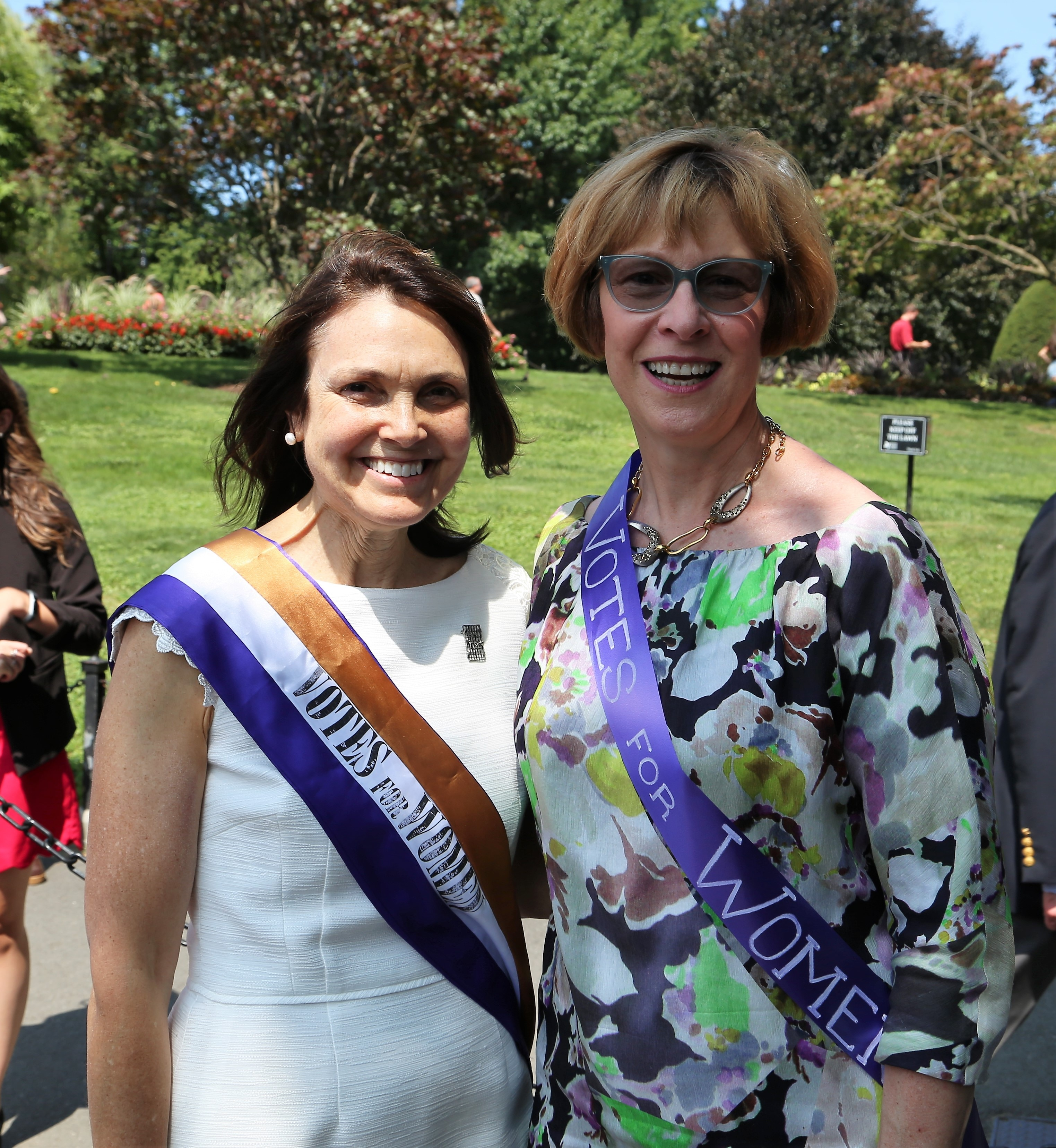 Auditor Bump with Fredie Kay, President of the Women's Suffrage Celebration, wearing suffragette sashes.