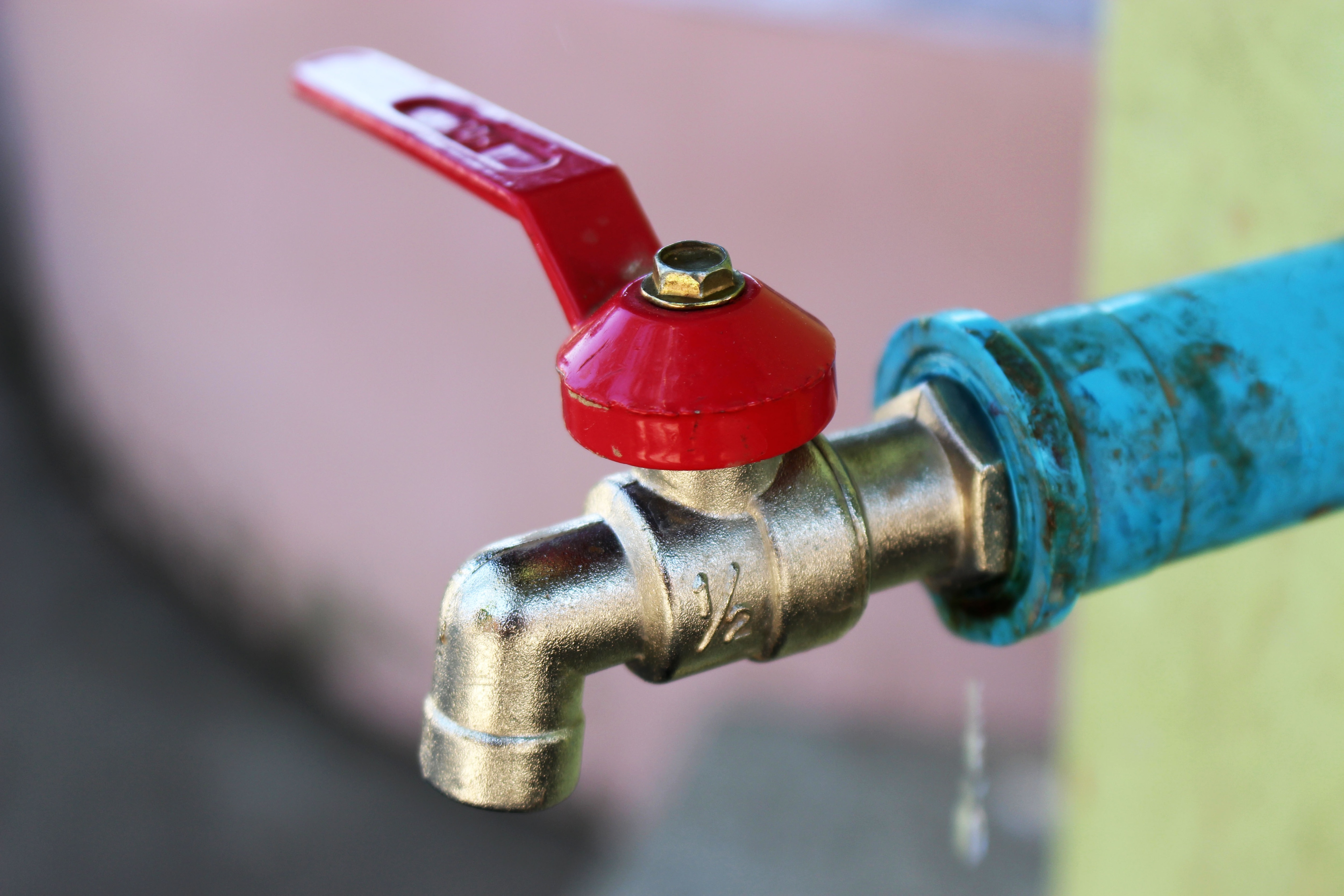 Outdoor water faucet with a red handle.