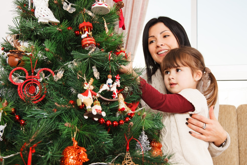 Mom and daughter hanging decorating Christmas tree