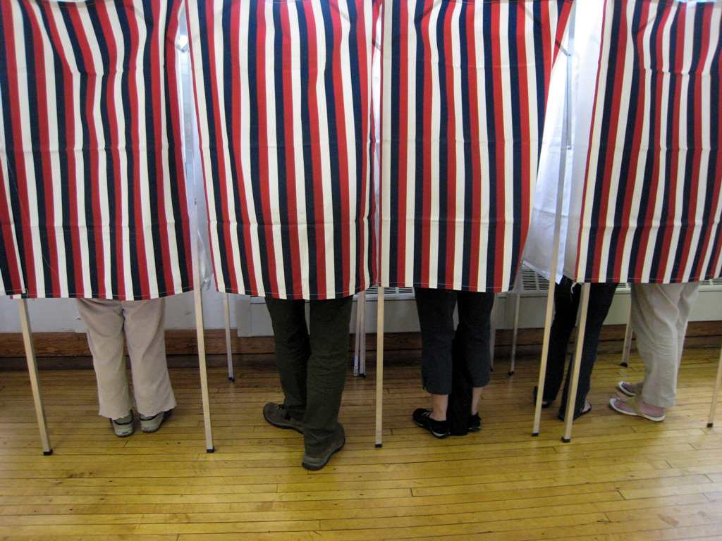 Voters stand behind striped curtains at voting booths while casting ballots
