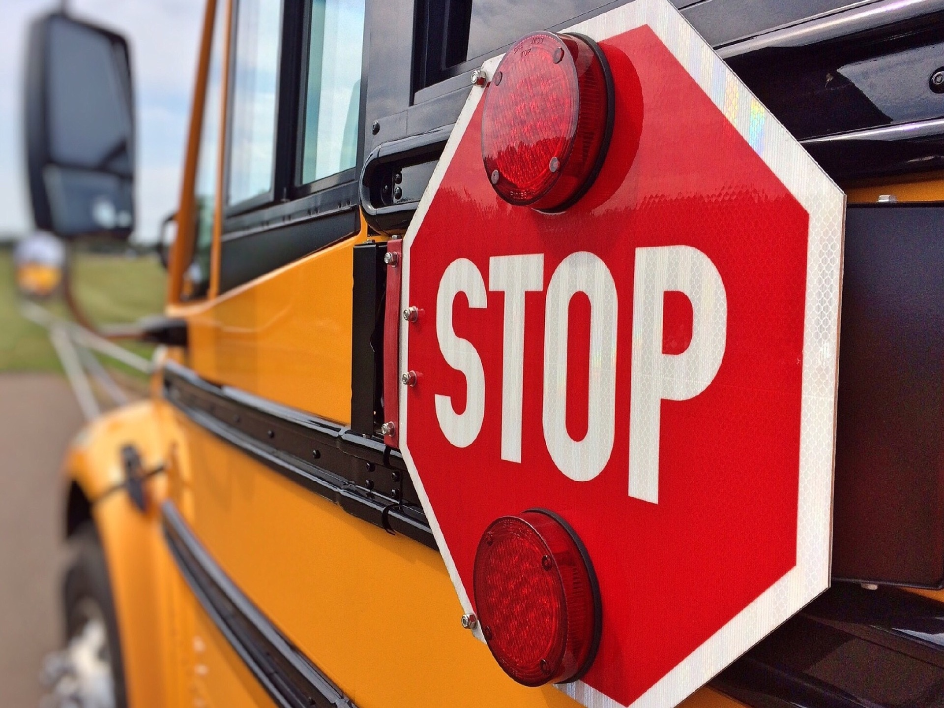 Stop sign on the side of a school bus.