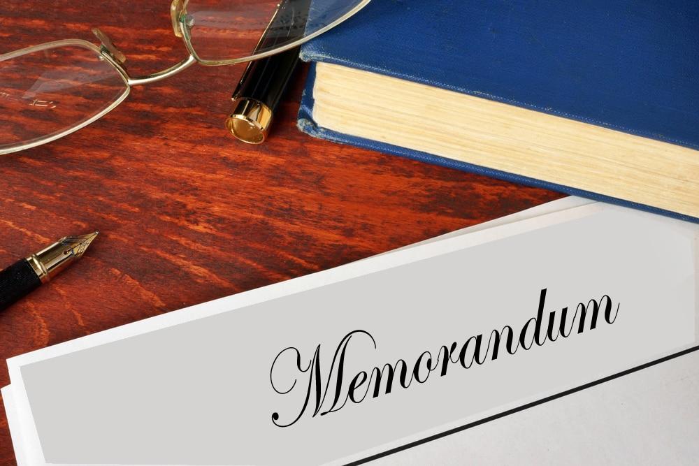 memorandum, pen and eye glasses on desk