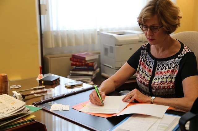 Auditor Bump writing a letter at her desk.