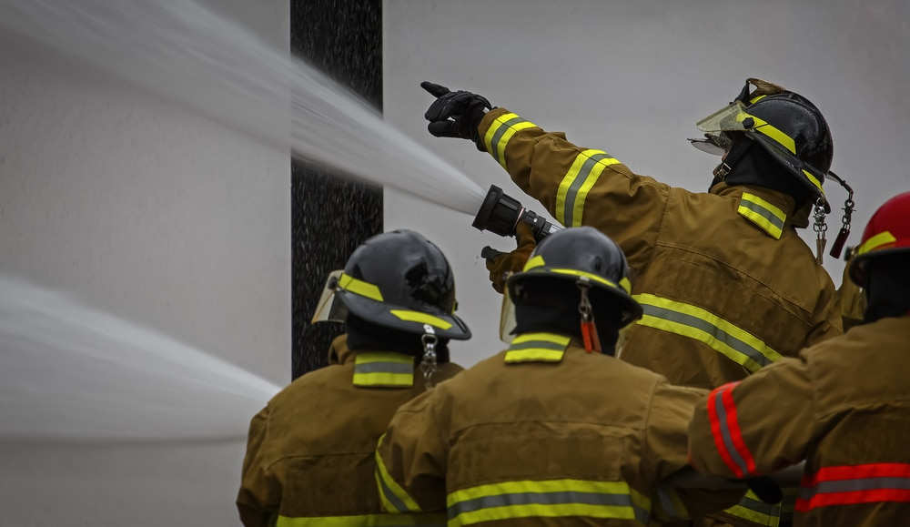 Three firefighters with hose and one pointing to direct them