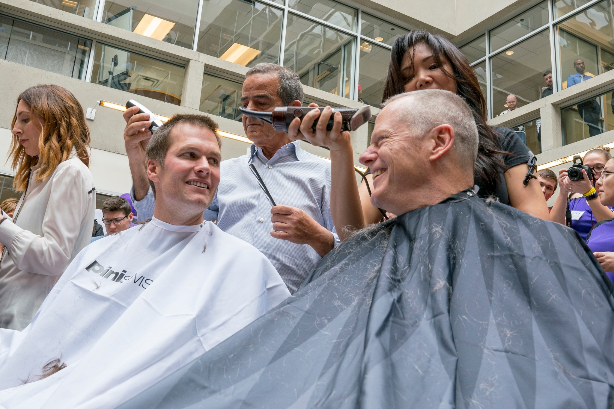 """Governor Baker and Tom Brady get buzz cuts during """"Saving by Shaving"""" event at Granite Telecom to benefit Dana-Farber."""