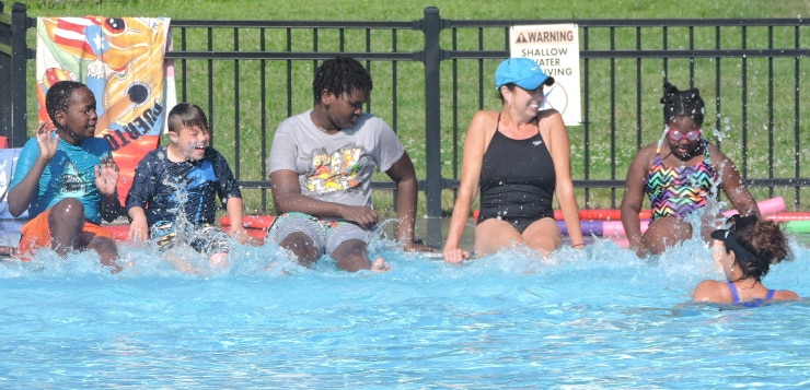 A photo of children, young adults, and an adult sitting on the edge of a pool and kicking their feet. A swimmer is in the water, facing them. There are colorful pool noodles and bodyboards behind them.