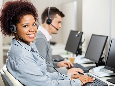 office worker at computer wearing headset