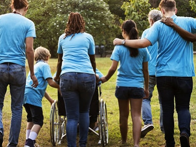 Image of a person in a wheelchair and several other ambulatory people in blue shirts.
