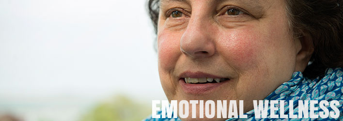 Photo of smiling woman with words EMOTIONAL WELLNESS underneath.