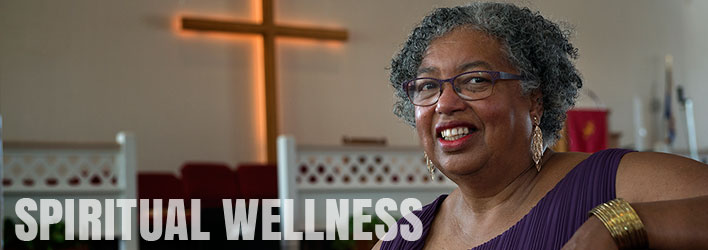 Photo of smiling woman sitting in church and the words SPIRITUAL WELLNESS written below.