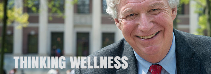 Photo of a smiling man wearing a suit and tie with the words THINKING WELLNESS below.