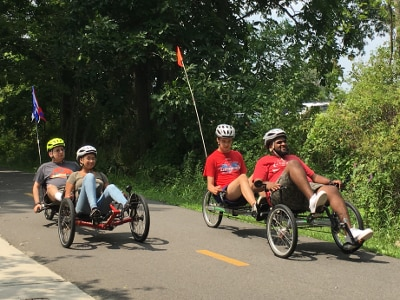 Four people are cycling on a bike path on a sunny day. Bushes and trees line the bike path. The cyclists are using tandem recumbent tricycles, with two people on each cycle. The cycles have flags on the back of them.