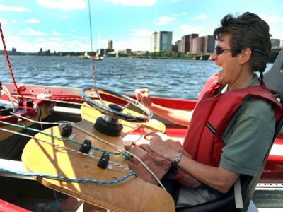 A woman is sitting in a sailboat in an upright seat with head support. In front of her is a board with a wheel and three spring-loaded cleats mounted on it. A green line and a white line are held in the cleats, with another white line and a blue line lying free on the board. The woman is gripping a knob on the wheel to turn it while she is laughing. Two other sailboats and the Boston skyline are visible behind her.