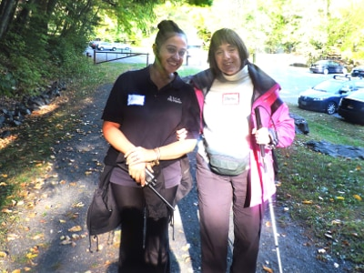 Two women are standing on a path in the woods, with a gate and a parking lot visible behind them. One of the women is holding a radio in one hand and holding her other elbow out from her body. The second woman is holding onto this elbow with one hand, and holding a white cane in the other hand. They are both smiling.