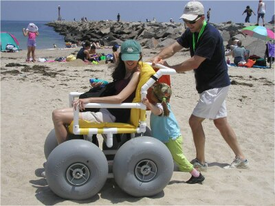 A woman is sitting in a beach wheelchair with yellow cushions and large balloon tires. A man and a small child with pigtails are pushing the woman across the sand on a beach, with a jetty behind them. The man and the woman are looking down at the small child and smiling.
