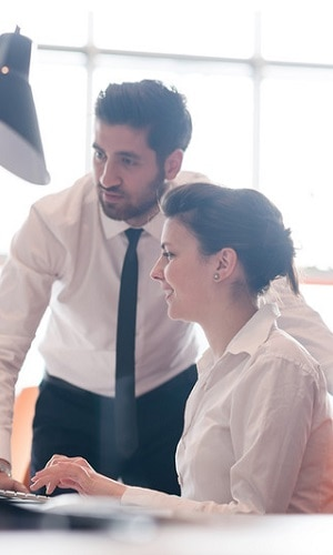 Man and woman in business attire working together on project at modern office