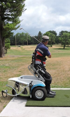 A man is using a ParaGolfer all-terrain wheelchair to raise himself to a standing position. He is swinging a golf club over his shoulder and looking down range.