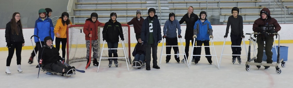 A group of fifteen skaters are standing next to each other. There are two ice sled users, one participant has ice grippers on his shoes, and the rest of them are using ice skates, five of whom are also using skate walkers as a balancing aid.