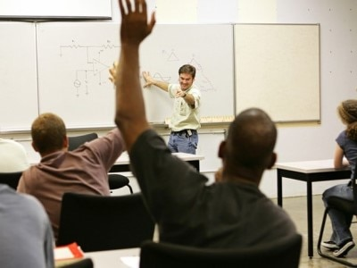 Classroom with teacher in front of whiteboard and seated students raising hands.