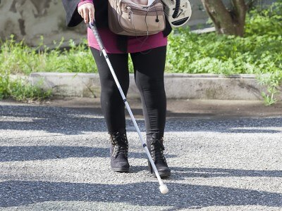 Woman using a white cane and crossing the street. The curb behind her does not have a curb cut.