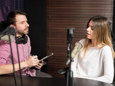 Man interviewing woman with microphone during podcast recording in studio