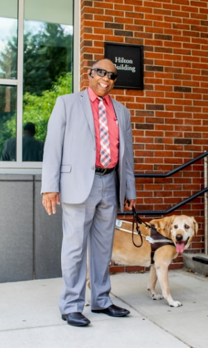 MCB Consumer Richard Phipps and his guide dog standing in business attire outdoors at Perkins School for the Blind
