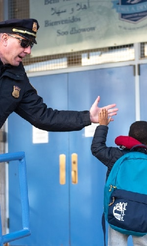 police officer high five student