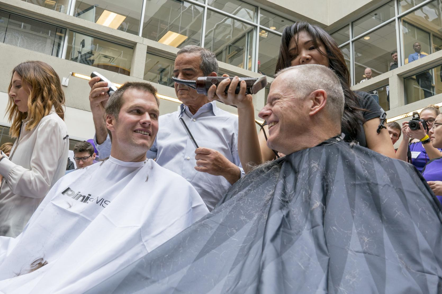 "Governor Baker and Tom Brady get buzz cuts during ""Saving by Shaving"" event at Granite Telecom to benefit Dana-Farber."