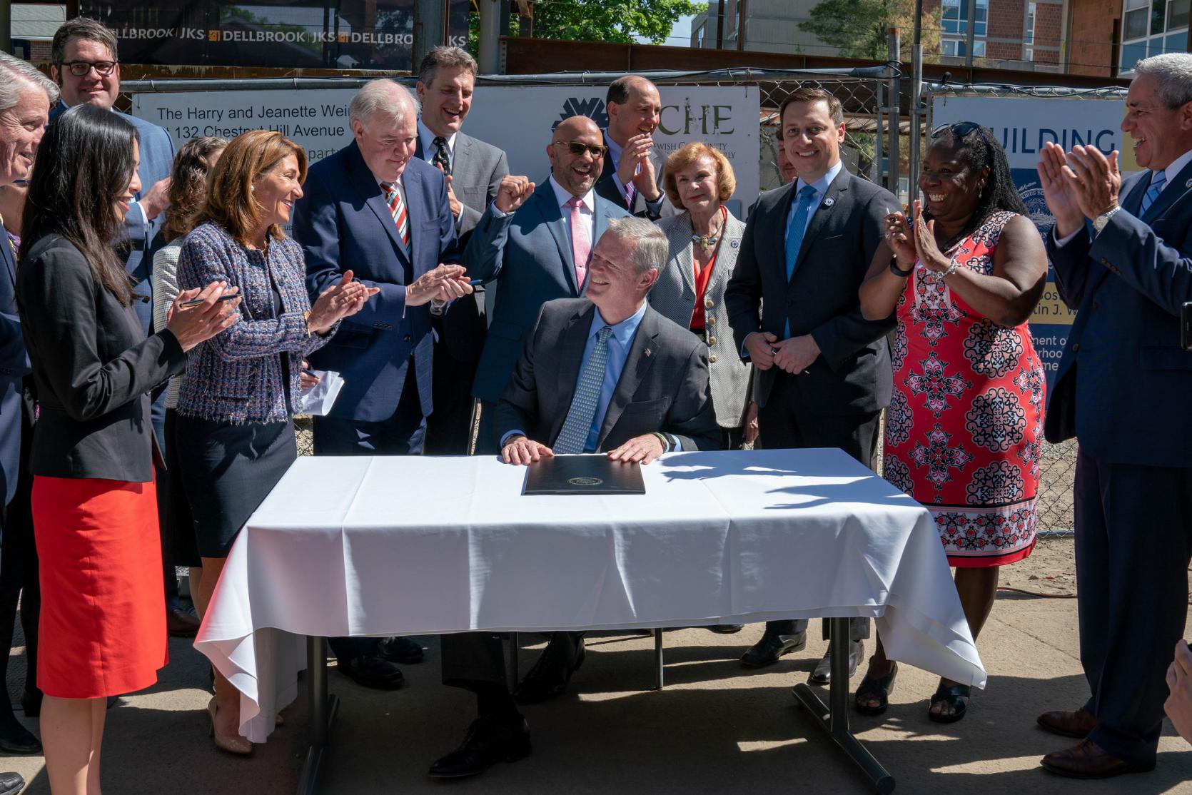 Governor Baker signs housing bond bill surrounded by legislators and other officials.