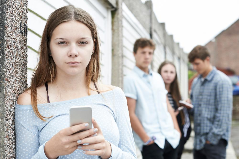 Shutterstock image of a teenager with a cell phone.