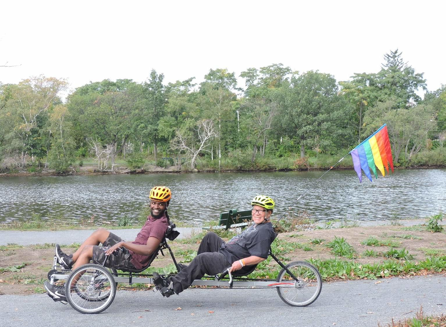 A photo of a younger man and an older man riding a recumbent tricycle together. They are both pedaling, and the younger man in front is also steering. They are smiling at the camera. Behind them is the Charles River.