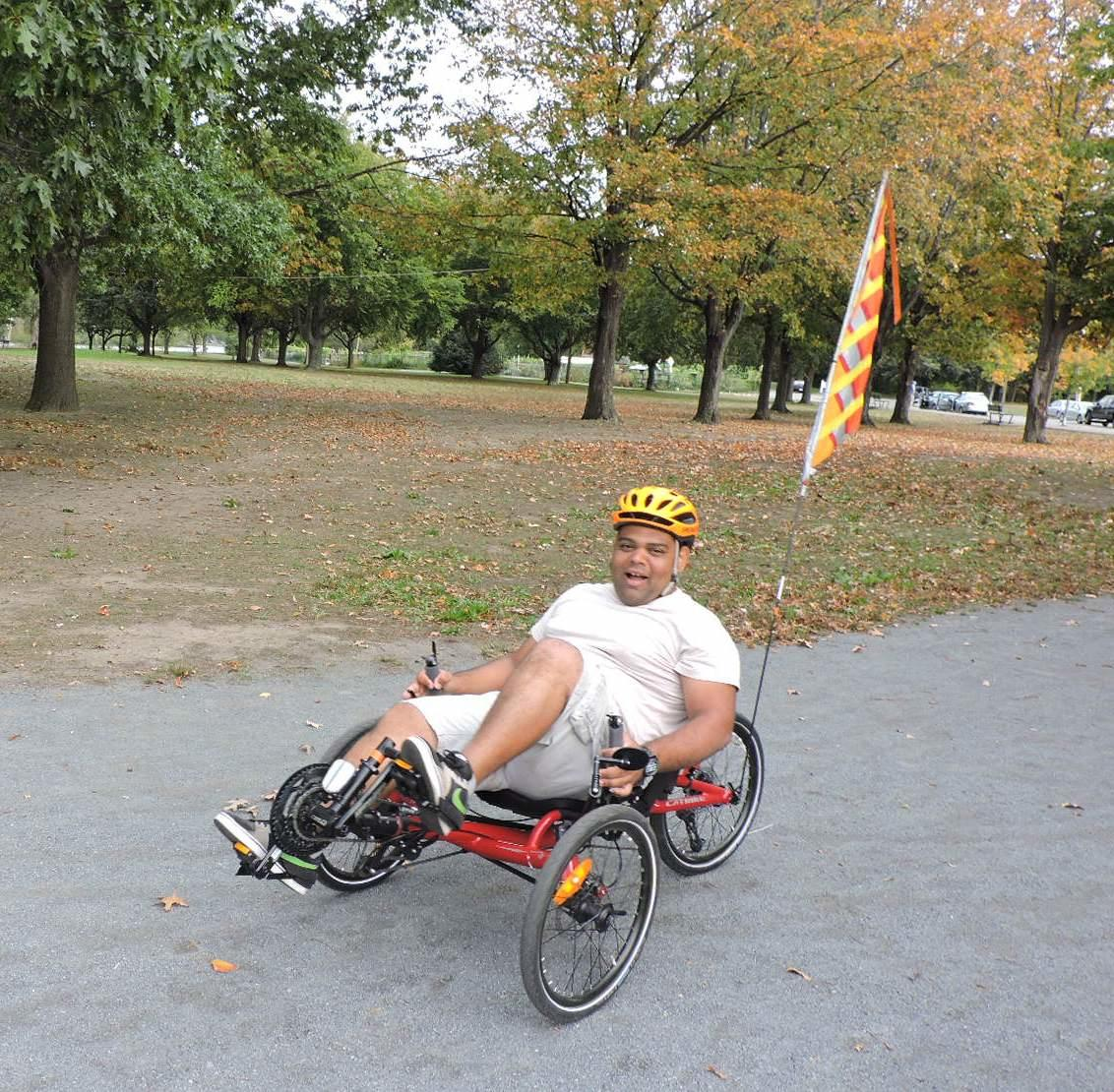 A photo of person riding a recumbent tricycle on a bike path, with a large lawn behind him. The trees on the lawn have green and orange leaves.