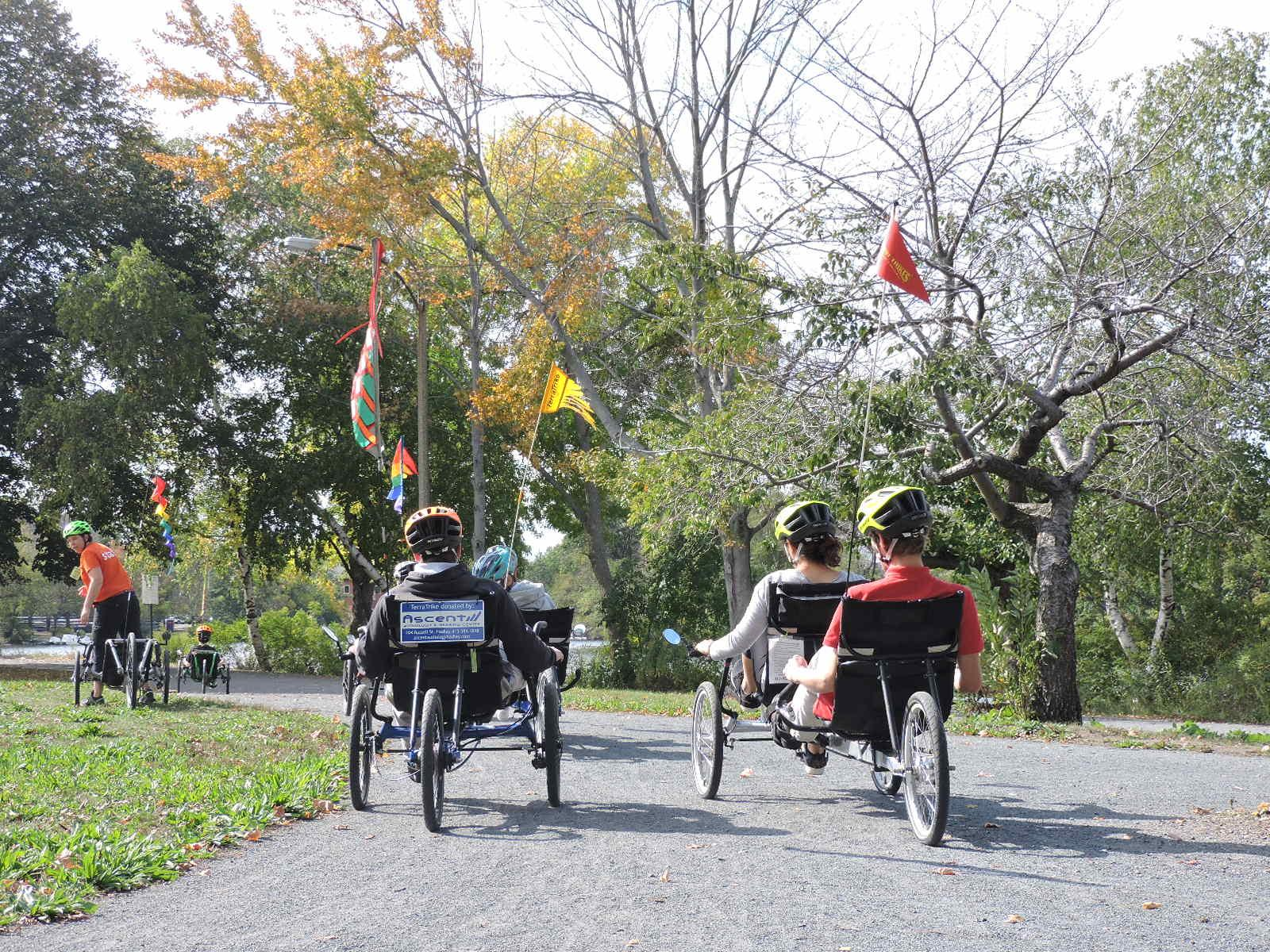 A photo of a group of recumbent cycles on a bike path next to a river. Some of the trees have yellow leaves. The cycles have colorful flags on them.