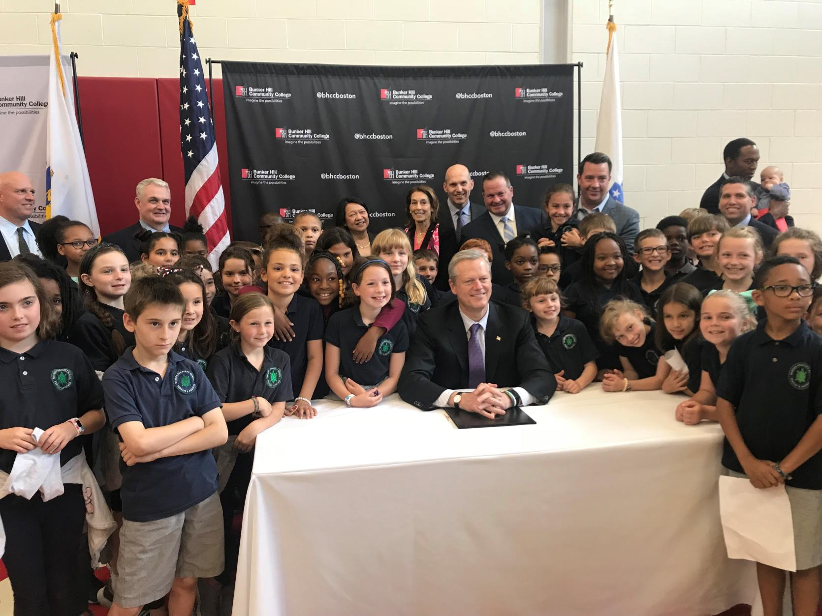 •	Gov. Charlie Baker is surrounded by third graders from Warren Prescott School in Charlestown as he announces $20 million in life science funding for 23 Massachusetts companies. Baker was also joined at Bunker Hill Community College by state officials and representatives of life science companies.