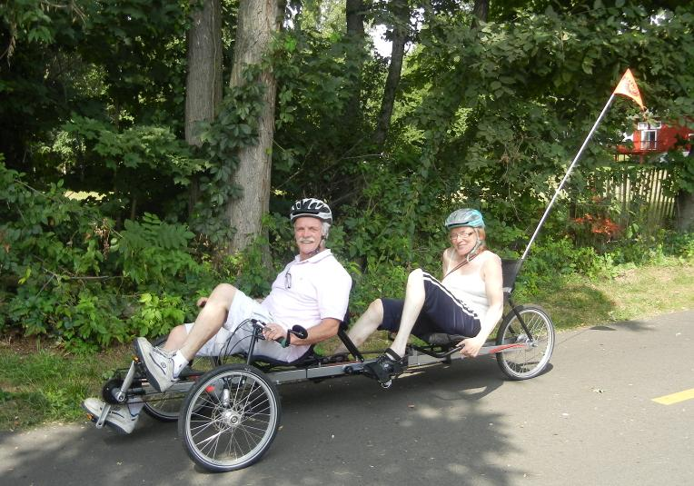 A photo of two cyclists riding a recumbent tandem tricycle. The cyclist in front is steering. The cyclist in back is using straps to hold her feet on the pedals.
