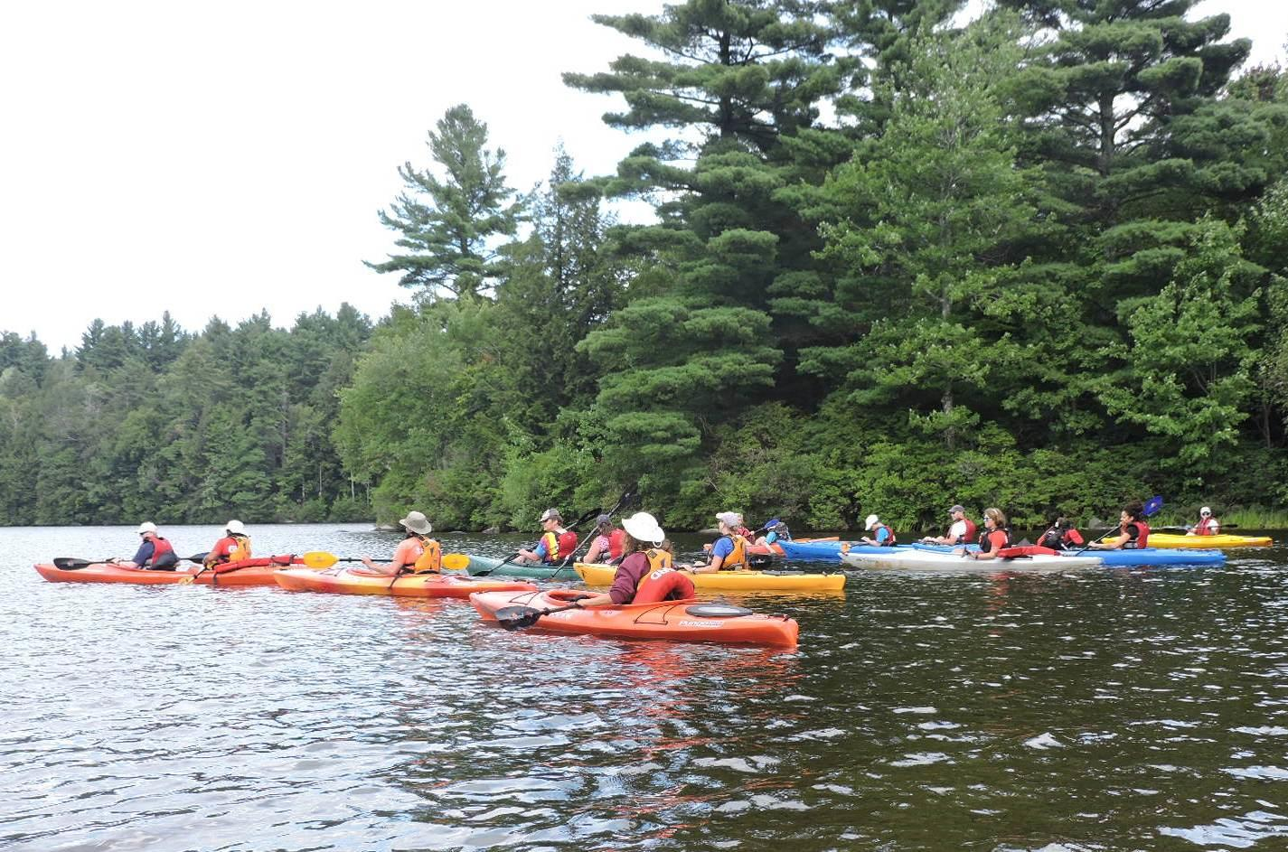 A photo of a large group of kayakers paddling close together. Some of the kayaks are single boats and some are tandem boats with two paddlers. Behind them is a wooded shoreline.