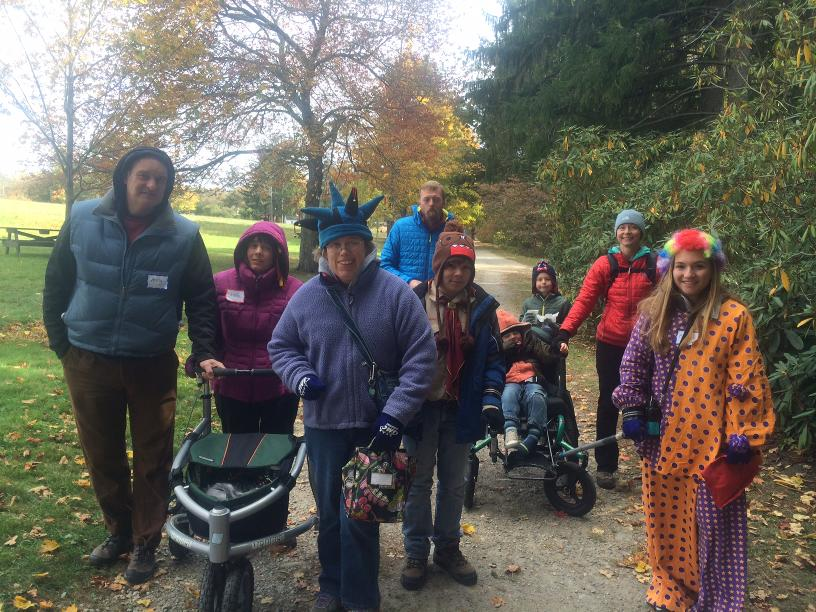 A photo of a group of hikers standing on a flat dirt trail. Some of the hikers are wearing colorful costumes. One hiker is using an all-terrain wheelchair with rickshaw poles on the front. Another hiker is using an all-terrain walker.