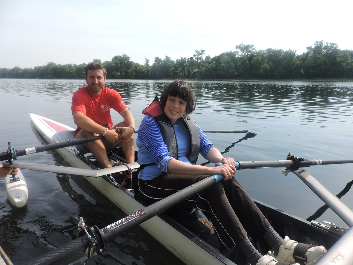 A photo of two rowers sitting in a rowing shell. The rowing shell has pontoons on it. The rower sitting in back is a lifeguard.