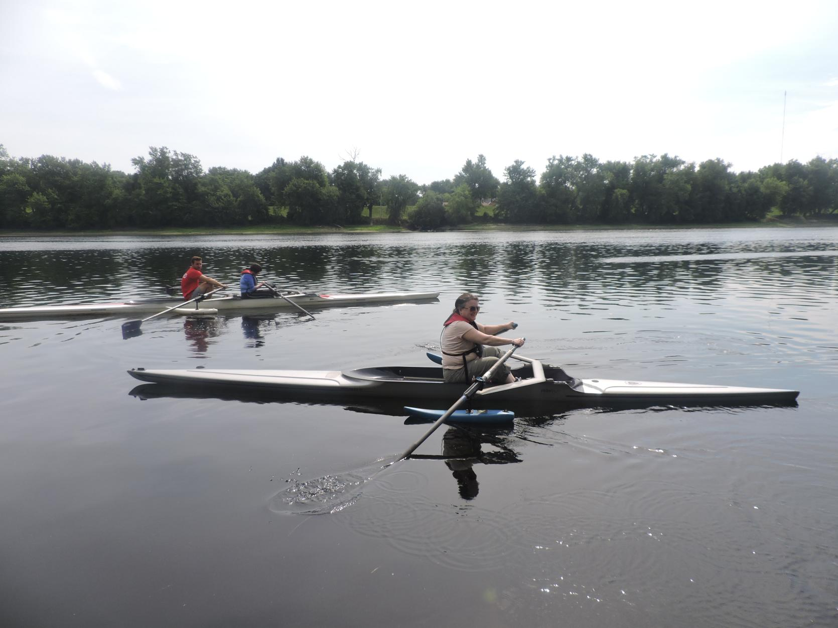 A photo of three rowers on the water. The rowers in the back are using a tandem rowing shell with pontoons. The rower in the front is using a single shell with pontoons.