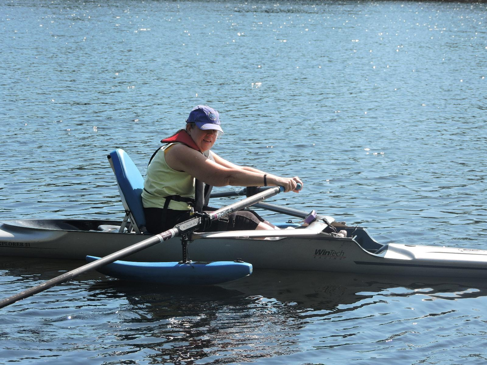 A photo of a woman rowing. She is using a shell with pontoons and an upright, padded seat.