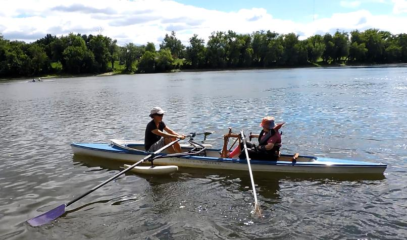 A photo of two rowers facing each other in a tandem shell with an open cockpit. There are pontoons on the shell. One of the women is using a device called a Front Rower, which allows her to row using only one arm. The device sits upright in the rowing shell, with an oar attached to one ride and a handle attached to the other. The rower is pulling on the handle to move the oar on the opposite side.
