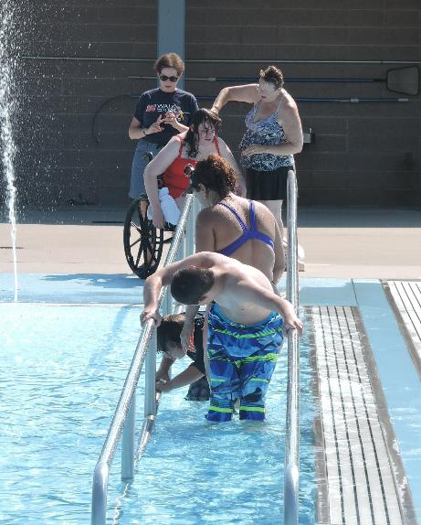 A photo of a group of people using a ramp to enter the pool. One of the people is using a wheelchair.