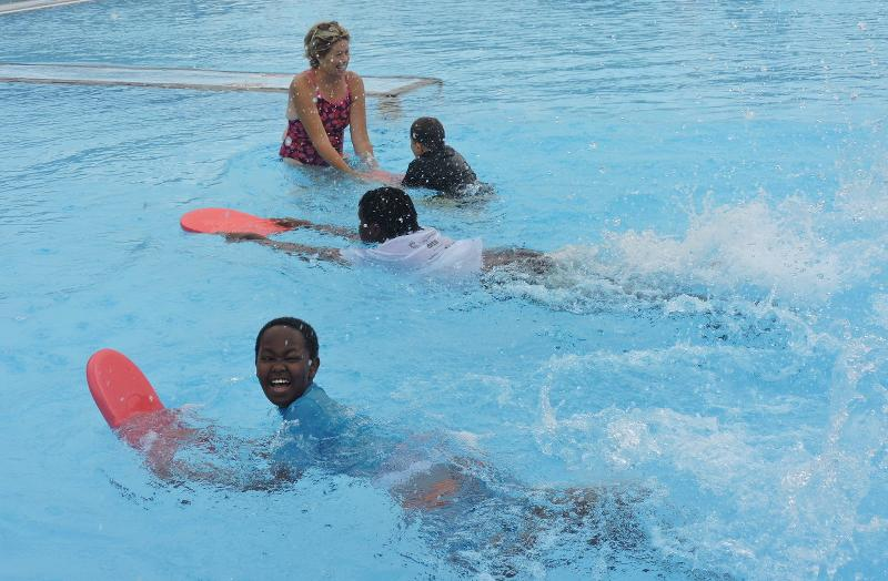A photo of three children swimming across the pool using bodyboards. One of the children is turning and laughing. One of the children has swum up to a woman who is holding his bodyboard.