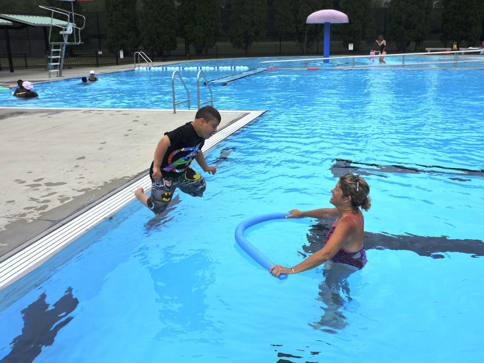 A photo of a young boy jumping into the water from the edge of a pool. A woman is standing in the water in front of him, holding a pool noodle in the water.