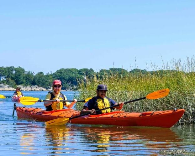 A photo of two people in a tandem kayak with a closed cockpit. Both people are paddling. Behind them is another tandem kayak with two paddlers.