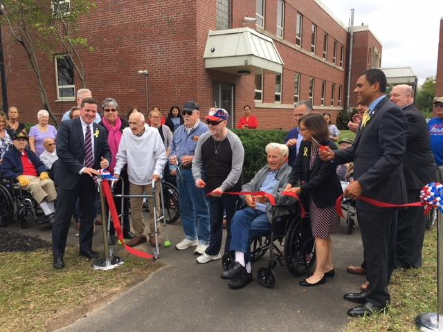 Ribbon Cutting l-r: Soldiers' Home in Holyoke Superintendent Bennett Walsh, Donna Archambault, veteran residents, Henry Salvas, Roger Thomas, Daniel Kennedy, Edward Wrobleski; Representative Brian Ashe, Secretary of Elder Affairs Alice Bonner; Department of Veteran Services Secretary Francisco Ureña; Senator Donald Humason