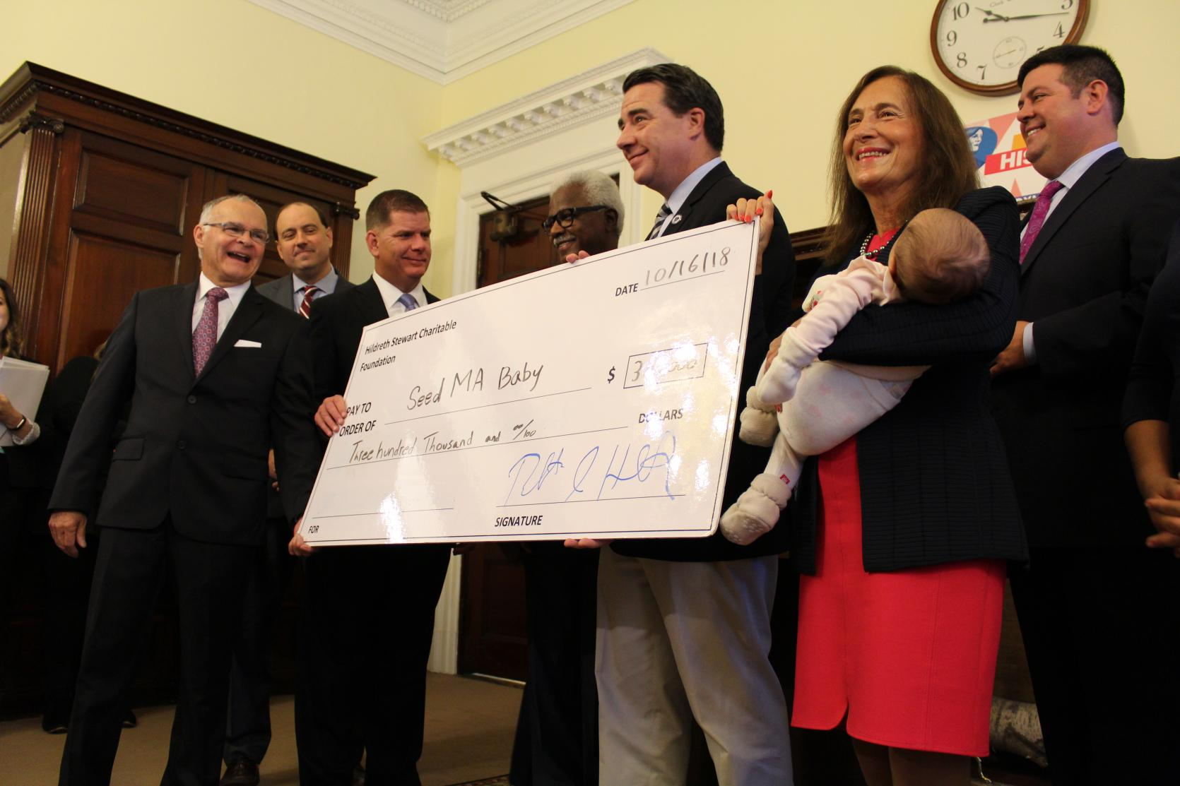 Photo of Treasurer Goldberg holding a baby in front a check for SeedMA Baby, standing across from Boston Mayor Marty Walsh