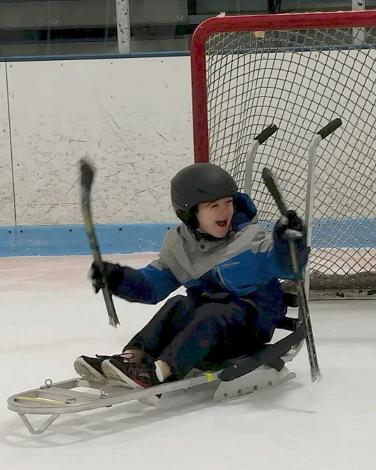 A young child is sitting in an ice sled in front of a small hockey net, holding a small hockey stick in each hand. The sled has handles on the back. The child is wearing a helmet and laughing.